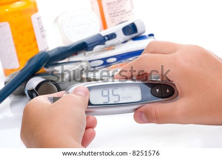 Kid is doing a diabetes glucose level finger blood test. In background there are older, bigger devices. Modern, mini monitor in her hands.