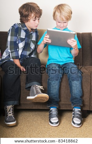Kid is working on a tablet computer while his brother is watching - stock photo