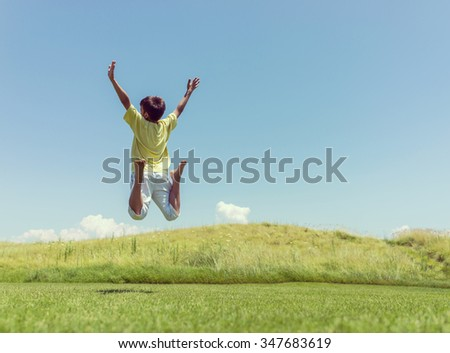 Kid jumping on beautiful field