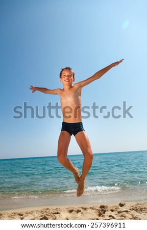 Kid jumping on the beach - stock photo