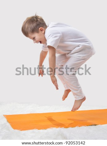 Kid jumps, doing yoga - stock photo