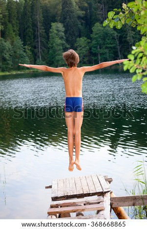 Kid jumps off a wooden dock into the water in a summer forest - stock photo