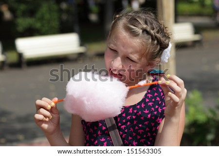 Kid licks cotton candy in the park - stock photo