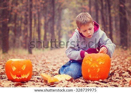 Kid lighting the jack-o- lantern in autumnal forest - stock photo