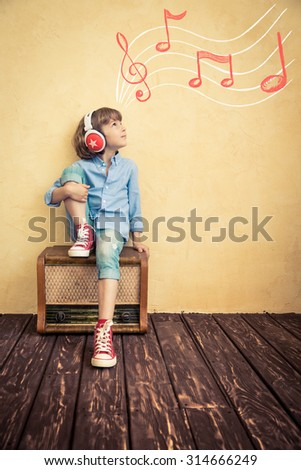Kid listen music at home. Hipster child with retro vintage radio - stock photo
