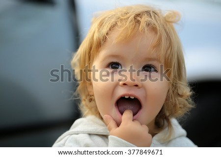 Kid little child baby boy fair-haired blond hazel-eyed wearing grey hooded coat cute portrait with finger in mouth on blurred car background, horizontal picture