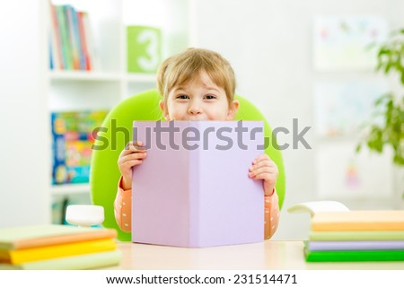 Kid little girl hiding behind book indoor - stock photo