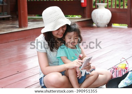 Kid looking and playing mobile phone with her mom on vacation time - stock photo