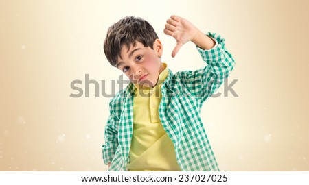 Kid making bad sign over ocher background