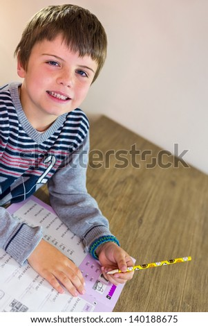 kid making his homework, with a smile - stock photo