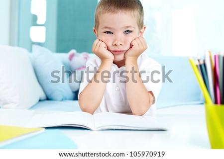 Kid not feeling like doing his homework - stock photo