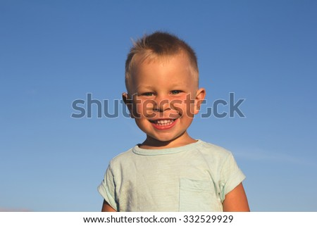 Kid on a beach laughing and playing in sunset light - stock photo