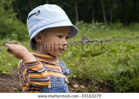Kid on coast of the wood river throws stones in water - stock photo