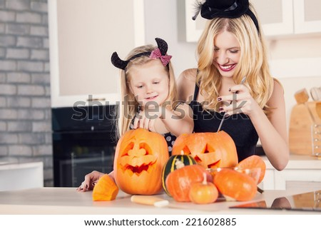 Kid on Halloween party making carved pumpkin with a little help from her mother - stock photo