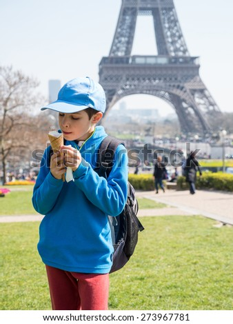 Kid outdoors portrait eating ice cream in front of Eiffel tower. Paris, France. - stock photo