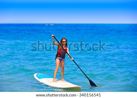 Kid paddle surf surfer girl with row in mediterranean beach - stock photo