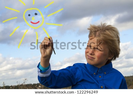 kid painting sun - stock photo