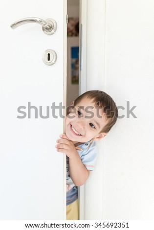 Kid peeking out of the open room door - stock photo