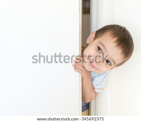 Kid peeking out of the open room door