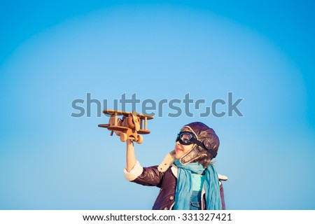 Kid pilot with toy wooden airplane against blue winter sky background. Happy child playing outdoors - stock photo