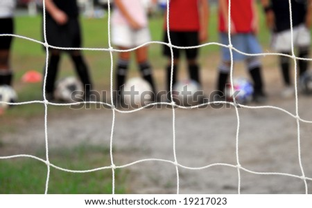 Kid players lined up behind soccer goal at practice - stock photo