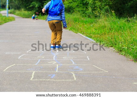 kid playing hopscotch on playground outdoors