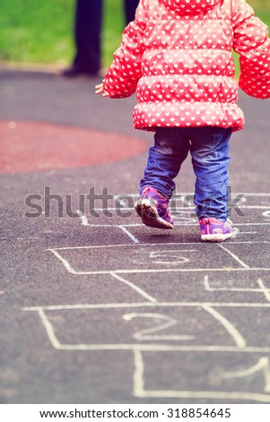 kid playing hopscotch on playground outdoors, children outdoor activities - stock photo