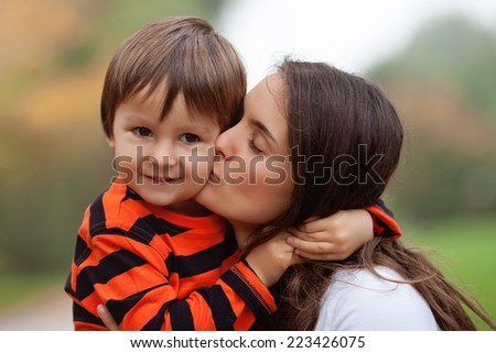 Kid playing isolated portrait. Young mother her boy outdoor in the park - stock photo