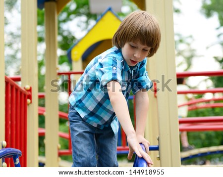 kid playing on  playground in summer outdoor park - stock photo