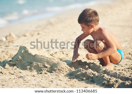 Kid playing on the beach in a sunny day. - stock photo