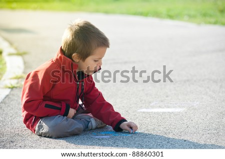 Kid playing on the ground with chalk. - stock photo