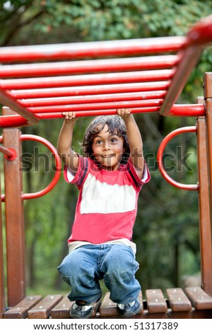 Kid playing on the monkey bars at the park - stock photo