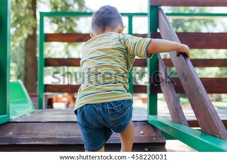 Kid playing outdoors. Child at the playground. - stock photo