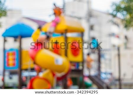 Kid playing playground blurred in park - stock photo