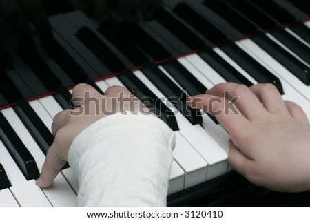Kid playing the piano during piano lesson - stock photo