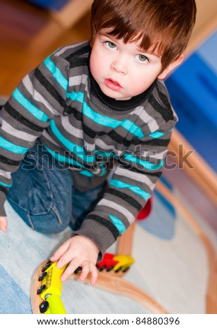 Kid playing with a toy train indoors - stock photo