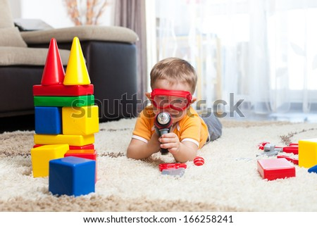 kid playing with building blocks and imagining himself a hero - stock photo