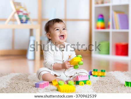 kid playing with building blocks at kindergarten - stock photo