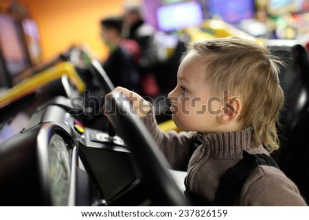 Kid playing with car simulator in the amusement park - stock photo