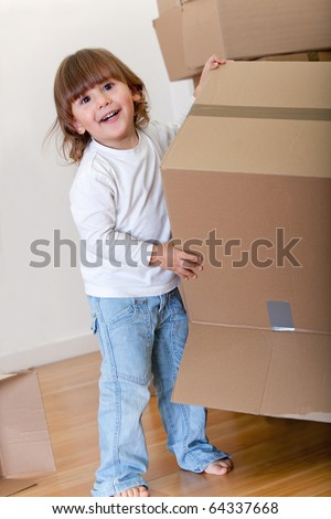 Kid playing with cardboard boxes excited about moving