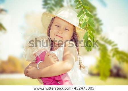 Kid playing with her doll. Closeup portrait head shot of smiling girl embracing, holding her doll looking at you camera isolated outdoors green background. Positive human emotions. Childhood concept - stock photo