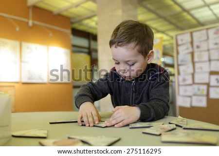 Kid playing with puzzle in the classroom - stock photo