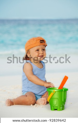 Kid playing with sand on the beach with scoop - stock photo