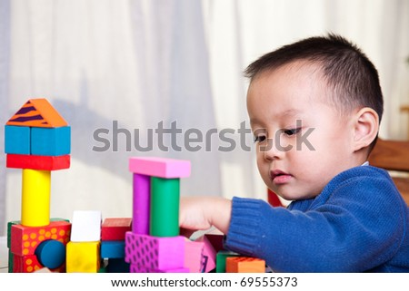 kid playing with toy blocks - stock photo