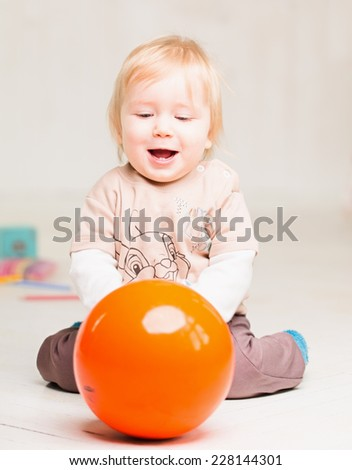 kid playing with toys on the floor in a bright room - stock photo