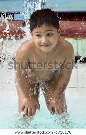 kid playing with water fountain in swimming pool - stock photo