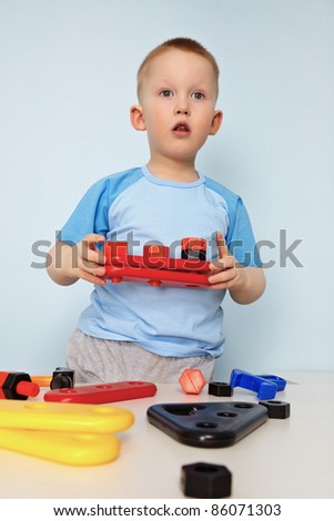 Kid plays with toy parts - stock photo