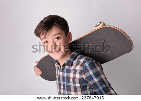 Kid portrait holding skateboard studio portrait. - stock photo