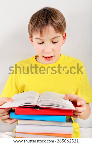Kid read the Book at the Home on the White Wall Background - stock photo