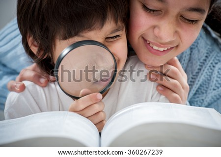 Kid reading and researching the book with magnifier - stock photo
